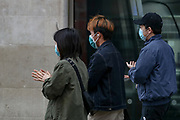 A group of Asian friends are seen cleaning their hands with hand sanitiser near Leicester Square in central London on Monday, May 11, 2020. <br />