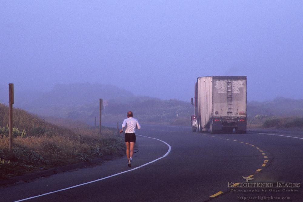 Runner on highway in fog with truck on road, near Manila, Samoa Peninsula, Humboldt County, CALIFORNIA