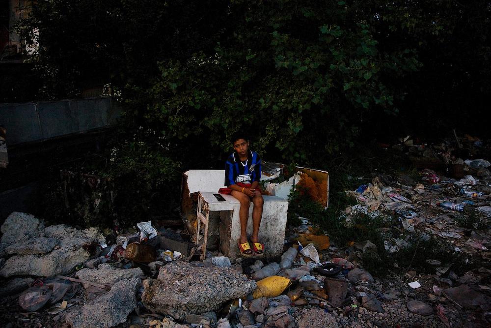 A boy sits on a pile of trash in the Nova Gazela settlement.