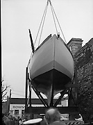 "The ""Asgard "" at Kilmainham Jail..1979..01.04.1979..04.01.1979..1st April 1979..The historic yacht ""Asgard"" owned by Erskine Childers was brought to Kilmainham Jail,Dublin. The vessel had to be hoisted ,by crane,over the outer wall of the jail. It was placed as part of a future exhibition to be set up by The National Museum..Image shows the Asgard in position prior to the lift of the yacht over the wall."