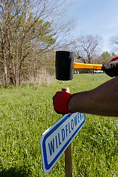 """Volunteers installing """"wildflowers"""" sign at Great American Seed Bomb event harnessing volunteers to plant natives prairie and wildflower seeds in North Texas prairies, Great Trinity Forest, Dallas, Texas, USA"""