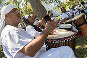 Descendants of enslaved Africans brought to Charleston in the Middle Passage hold a drum circle to honor their relatives lost during a remembrance ceremony at Fort Moultie National Monument June 10, 2017 in Sullivan's Island, South Carolina. The Middle Passage refers to the triangular trade in which millions of Africans were shipped to the New World as part of the Atlantic slave trade. An estimated 15% of the Africans died at sea and considerably more in the process of capturing and transporting. The total number of African deaths directly attributable to the Middle Passage voyage is estimated at up to two million African deaths.
