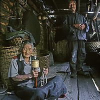 CHINA, TIBET. Elderly Menba mother & son relax on porch in remote Payi village, near mouth of Tsangpo River Gorge in eastern Himalaya. Note Buddhist prayer wheel & rosary beads.