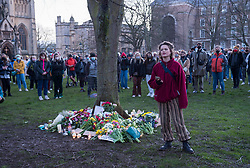© Licensed to London News Pictures;13/03/2021; Bristol, UK. A woman performs a poem as hundreds of people defy covid lockdown restrictions on public events to lay flowers and notes in remembrance on College Green in memory of woman Sarah Everard whose body was confirmed found in Kent yesterday. A police officer has been charged with her murder. Vigils across the the country had been planned but were supposed to be cancelled because of the Covid-19 coronavirus pandemic Lockdown restrictions in England. Photo credit: Simon Chapman/LNP.