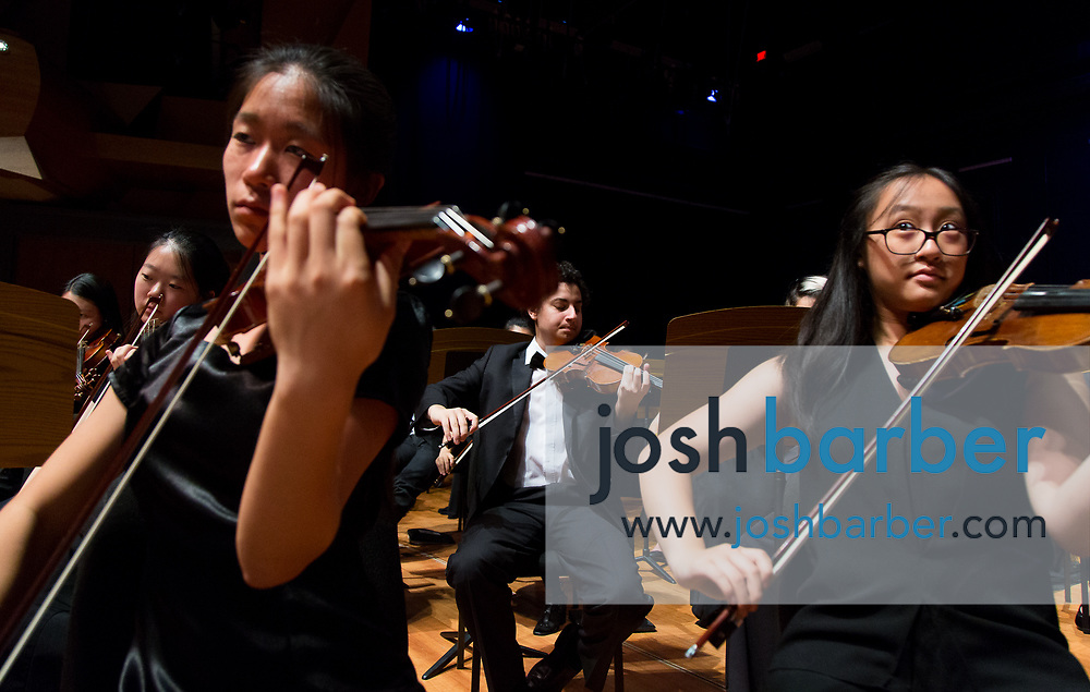 Violinists Elaine Huang of Beckman High School String Orchestra, foreground-left, Noam Elisha of Orange County Youth Symphonic Orchestra, background-center, and Julia Wang of OCYSO play during a dress rehearsal for a joint performance at Chapman University's Julianne Argyros Orchestra Hall on Sunday, May 14, 2017 in Orange, Calif. (Photo by Josh Barber, Orange County Register Contributing Photographer)