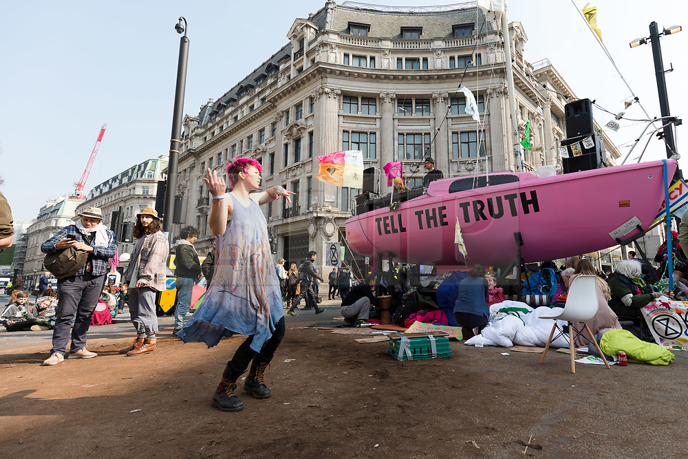 © Licensed to London News Pictures. 17/04/2019. A protester dances in the road as environmental activists from the Extinction Rebellion movement continute to protest and block the road at Oxford Circus as part of a series of direct actions taking place across the capital. The protests demand urgent action from governments on climate change. Photo credit: Vickie Flores/LNP