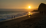 28 JULY 2018 -- MALIBU, Calif. -- Families enjoy the sunset as waves crash onto the beach at Sycamore Cove Beach in Pt. Mugu State Park in Malibu, Calif., Saturday, July 28, 2018. The state park is part of the Santa Monica Mountains National Recreation Area, and features five miles of ocean shoreline. Photo © copyright 2018 Sid Hastings