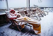 The deckchair man, tourist fallen asleep on deck of cruise ship, covered by fresh snowfall, Amundsen Sea, Antarctica.