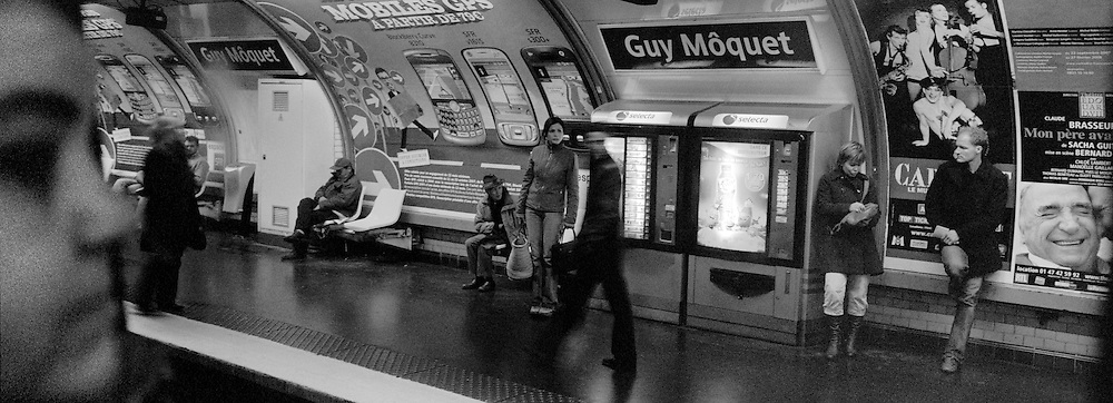 Commuters wait on the platform at Guy Moquet Metro station in Paris, France. October 12, 2007. Photo Tim Clayton..Paris is often known as 'The City of Love' but like any major City in the world, the inhabitants often live a singular existence, going about their daily lives in relative solitude. Parisians are respectful of each others space, often courteous and polite while extremely conscious of their own image. While love can be seen openly around the streets of Paris, so can the separate lives of Parisians.