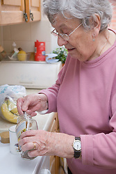 Older woman making herself a cup of coffee,