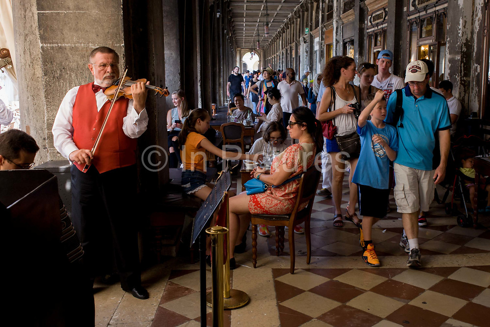 Violinist plays inside the covered Procuratie Nuovo in Piazza San Marco, Venice, Italy. The orchestra plays for cafe customers in the heart of Venice where visitors either sit at tables or walk in the shade from a midsummer heatwave. The violinist looks serious and hopes for tips. Venice attracts 22-million visitors each year (for a city of only about 60,000 residents) while the cultural protection organisation, Italian Nostra, warns that Venice can only accommodate about 33,000 visitors per day but currently at least 60,000 daily.