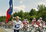 Dore Holte of Seattle, Wa., left, runs with the Texas flag as riders pedal past during the 9th stage of the Tour de France cycling race between Saint-Leonard-de-Noblat and Gueret, central France, Tuesday, July 13, 2004. (AP Photo/Laurent Rebours)
