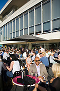 Men and women enjoy the sunshine and drink and eat at tables outside the Royal Festival Hall on the South Bank, London, UK