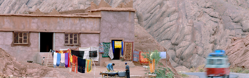 Laundry and home with bus driving by and vendors selling, Dades Gorge