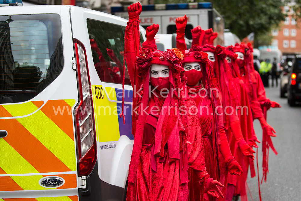 Extinction Rebellion's Red Rebel Brigade attend a protest outside the Department for Transport by activists from HS2 Rebellion on 4 September 2020 in London, United Kingdom. Activists glued themselves to the doors and pavement outside the building and sprayed fake blood around the entrance during a protest which coincided with an announcement by HS2 Ltd that construction of the controversial £106bn high-speed rail link will now commence.