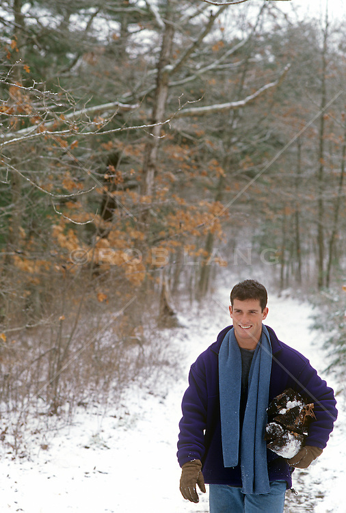 man walking down a snow covered path in the woods with firewood under his arm