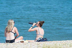 © Licensed to London News Pictures 22/07/2021. Whitstable, UK. Friends sunbathing on the beach. Another hot heatwave day as people enjoy a day out at Whitstable in Kent. Photo credit:Grant Falvey/LNP