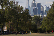 Youth football players warm up by running around part of Ruskin Park with the skyline of the City of London's financial district, on 8th August 2018, in London, England.