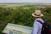 A country rambler looks out across Northwood Hill's landscape below, an wildlife area near Halstow on the Kent Thames estuary marshes, potentially threatened by the future London airport.