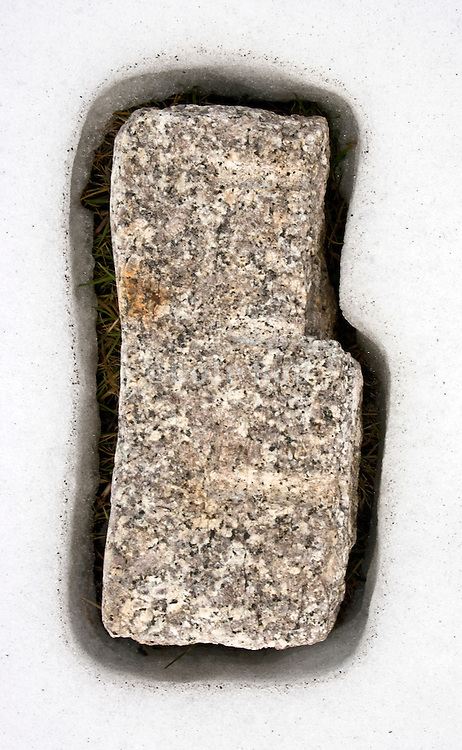 a stone laying in the grass which has warmed up and melted the snow away around its edges