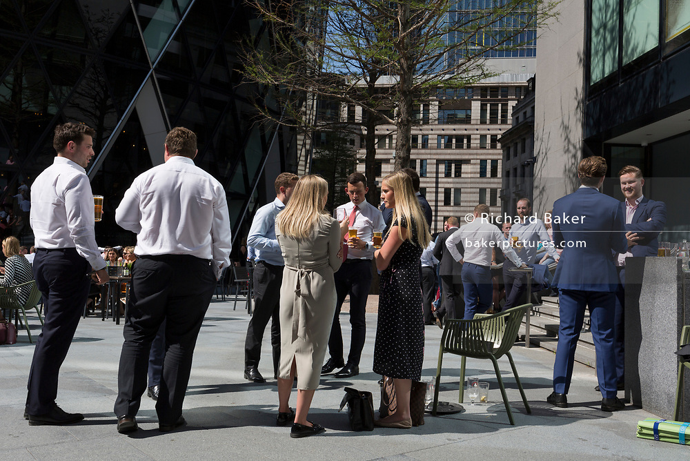Lunchtime City workers enjoy drinks in summer sunshine outside the Swiss Re building (aka The Gherkin), in the City of London, the capital's financial district (aka the Square Mile), on 22nd August 2019, in London, England.