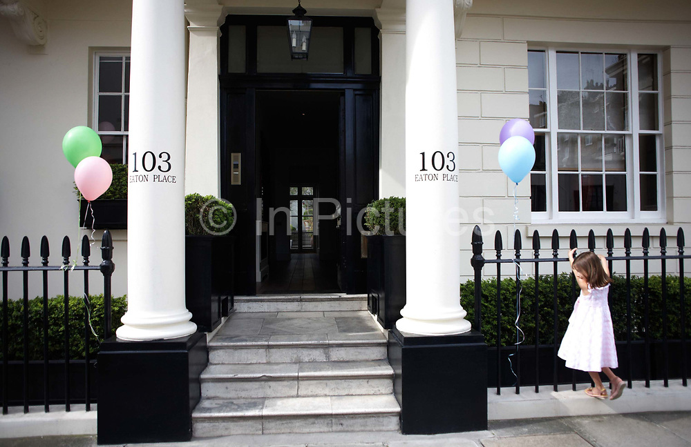A young girl hangs from railings where her helium-filled  birthday balloons signal the party is soon to commence as her mother prepares indside their fine house in an exclusive and classically-designed location in Belgravia, London. The pastel-coloured balloons rise up in a breeze as the girl is self-absorbed on her big day. 103 Eaton Place faces Eaton Square, one of London's three garden squares built by Thomas Cubitt and the Grosvenor family when they developed the main part of Belgravia from 1826 until 1855. Belgravia attracts actors, politicians, ambassadors, big-budget bankers, traders and Prime Ministers like Neville Chamberlain and Stanley Baldwin at number 93.