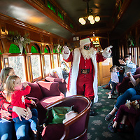 """STRASBURG, PA:  Dave Saunders, 46<br /> in his 7th year as Santa, greets passengers riding a holiday attraction """"Santa Express, on the oldest continually operated railroad in the country, in Strasburg, PA on December 13, 2020. The pandemic has forced difficult decisions about maintaining the holiday tradition of visits to Santa Claus versus safety concerns.  Plexiglass dividers, face shields, and physical distancing are among the precautions for those locations that have proceeded with Santa photo opportunities.  CREDIT:  Mark Makela for The New York Times"""