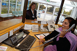 Receptionist on phone at work in NHS hospital Bradford Yorkshire UK