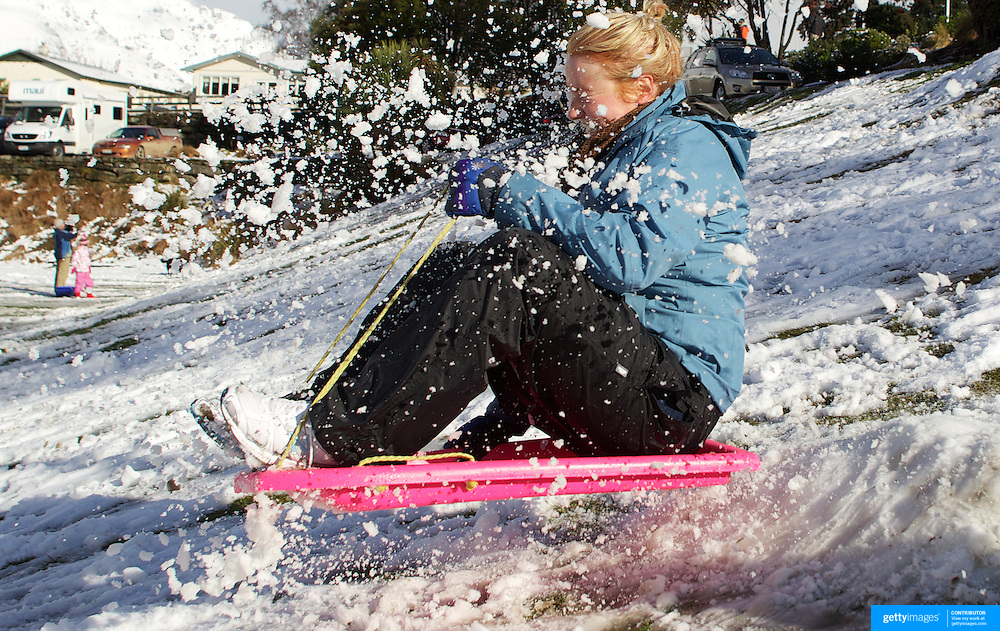 Alex Frankpitt, 22, from Christchurch has fun in the snow on a sledge in the Queenstown Recreation Grounds after fresh winter snow falls. Queenstown, Central Otago, South Island, New Zealand. 10th July 2011. Photo Tim Clayton.