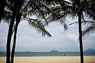 Two coconut palms frame a view of Cua Dai Beach in Hoi An, Vietnam, Southeast Asia
