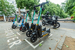 © Licensed to London News Pictures. 22/06/2021. LONDON, UK.  Rental e scooters parked up at a designated parking area on the King's Road in Chelsea.  These form part of a trial e scooter rental scheme launched on Monday 7 June, running for an initial 12 months, allowing pedestrians to hire an dride them legally, but only in certain boroughs of the capital as long as the regulations are observed.  By contrast, privately owned e scooters, although popular for many, remain illegal on public roads and pavements.  Photo credit: Stephen Chung/LNP