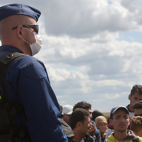 Police officer in health protection mask stands guard at a collection point of illegal migrants near Roszke (about 174 km South of capital city Budapest), Hungary on September 07, 2015. ATTILA VOLGYI