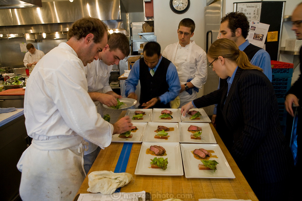 Stone Barns Center for Food and Agriculture at Blue Hills. Pocantico Hills, New York State. Dan Barber, chef, at left puts garnishes on meat dish.  (Chef Dan Barber is mentioned in the book What I Eat: Around the World in 80 Diets.)