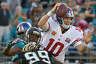 New York Giants quarterback Eli Manning (10) is sacked by Jacksonville Jaguars defensive tackle Sen'Derrick Marks (99) and defensive end Ryan Davis (59) on the Giants' final possession of the second half of an NFL football game in Jacksonville, Fla., Sunday, Nov. 30, 2014. Manning fumbled on the play. The Jaguars won 25-24.(AP Photo/Phelan M. Ebenhack)