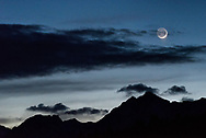 The sliver of a waxing moon moves towards the mountains in Grand Teton National Park.