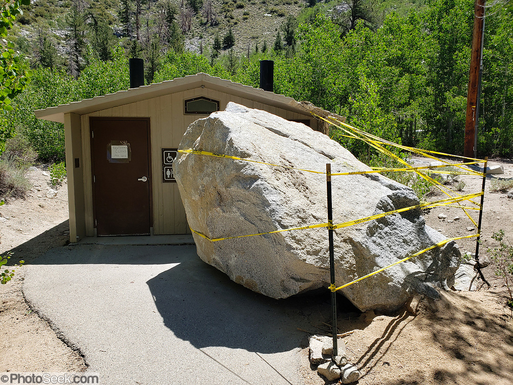 This giant boulder tumbled from cliffs above and nicked the corner of this restroom at Sabrina Campground, in Inyo National Forest, Mono County, California, USA.