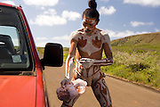 Rapa Nui man painting his body on side of the road  Easter Island, Chile