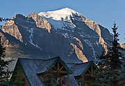 Mount Temple (3543 metres  or 11,624 feet) rises high above houses at Lake Louise townsite, Banff National Park, Alberta, Canada. This is part of the big Canadian Rocky Mountain Parks World Heritage Site declared by UNESCO in 1984.