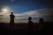 Soldiers are standing guard at night, while listening to the enemy's shelling, ready to run for cover in the trenches if being targeted, on the frontline of Hranitne, near Mariupol, southeast Ukraine.
