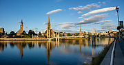 """Inverness, the administrative capitol of the Highlands, reflects in River Ness, in Scotland, United Kingdom, Europe. A settlement was established here by the 500s AD with the first royal charter being granted by King David I in the 1100s. The Gaelic king Mac Bethad Mac Findláich (MacBeth) whose 11th-century killing of King Duncan was immortalised in Shakespeare's largely fictionalized play Macbeth, held a castle within the city where he ruled as Mormaer of Moray and Ross. Inverness lies near two important battle sites: the 11th-century battle of Blàr nam Fèinne against Norway which took place on The Aird and the 18th-century Battle of Culloden which took place on Culloden Moor. Inverness means """"Mouth of the River Ness"""" in Scottish Gaelic. Surveys place it as one of the happiest places in the UK. This image was stitched from several overlapping photos."""