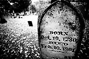 Very old headstone next to an open area with headstones in the distance. Black and White, Eery Gravestones.