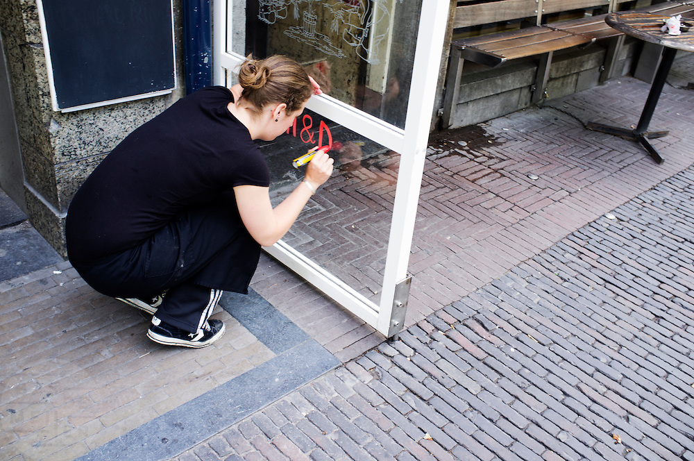 Een medewerkster van Kafe België in Utrecht schrijft een mededeling op een glazen bord voor het café.<br /> <br /> An employee of the cafe België in Utrecht is writing notes on a glass board.