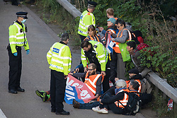 Ockham, UK. 21st September, 2021. Surrey Police officers monitor Insulate Britain climate activists who had blocked the anticlockwise carriageway of the M25 between Junctions 9 and 10 as part of a campaign intended to push the UK government to make significant legislative change to start lowering emissions. Both carriageways were briefly blocked before being cleared by Surrey Police. The activists are demanding that the government immediately promises both to fully fund and ensure the insulation of all social housing in Britain by 2025 and to produce within four months a legally binding national plan to fully fund and ensure the full low-energy and low-carbon whole-house retrofit, with no externalised costs, of all homes in Britain by 2030.