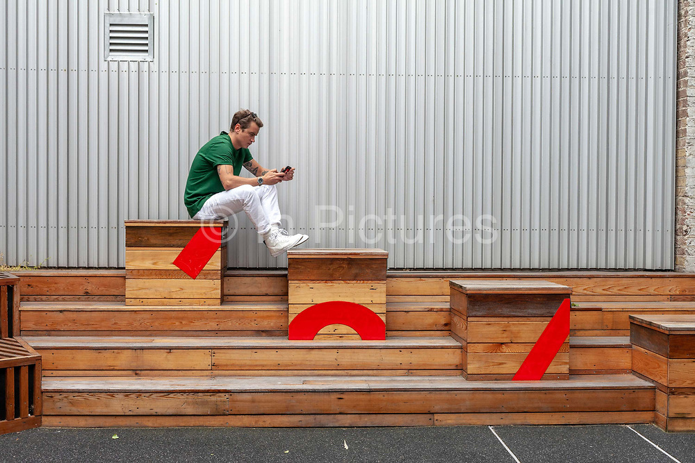 A man sits on wooden benches whilst using his mobile telephone in Shoreditch, London, United Kingdom.