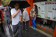 London, UK. Sunday 23rd August 2015. Heavy summer rain showers in the West End. People brave the wet weather armed with umbrellas and waterproof clothing. Chinese woman checking her mobile phone on Gerrard Street in Chinatown.