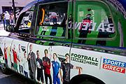 International footballers on the side of a London taxi, the reflection of a Balenciaga billboard plus New Bond Street shoppers, on 16th July 2021, in London, England. Balenciaga is a fashion house founded in 1917 by Spanish designer Cristóbal Balenciaga in San Sebastián, Spain.