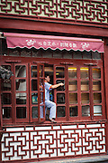 A worker cleans the windows of the Huxinting Teahouse in Yu Yuan Gardens Shanghai, China