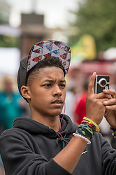 Teenage boy taking a photograph UK