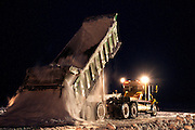 Alaska, North Slope. A maxi haul dumps a load of snow during ice road construction.