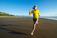 Young woman running on the beach at sunset in Manzanita, Oregon.